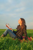 Teen girl reading the Bible outdoors Royalty Free Stock Photo