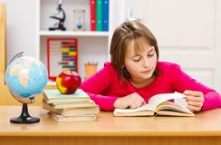 Teen girl reading book. In classroom royalty free stock photo