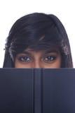 Teen girl reading book. Teen indian girl looks up from book Stock Photos