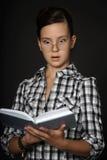 Teen girl reading a book stock photo