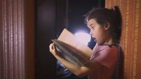 Teen girl reading book education is wall indoor stock video