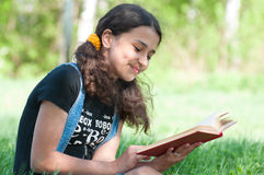 Teen girl reading  book on nature Royalty Free Stock Images