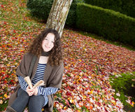 Teen Girl Reading Book Outside during the Autumn Season Stock Photos
