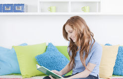 Teen girl reading. Book in room stock images