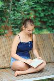 Teen girl reading a book. And dreaming in summer garden royalty free stock photo