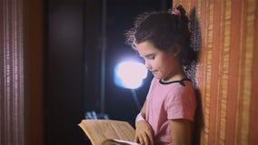 Teen girl reading book is wall indoor education stock video footage