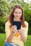 Teen girl reading electronic book. Outdoors Stock Photography