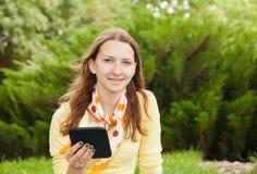 Teen girl reading electronic book. Teen girl reading an electronic book outdoors Royalty Free Stock Photo