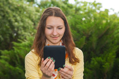 Teen girl reading electronic book. Outdoors Royalty Free Stock Photography