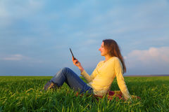 Teen girl reading electronic book. Outdoors at summer time Stock Image