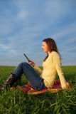 Teen girl reading electronic book outdoors. Teen girl reading electronic book sitting outdoors Stock Photo