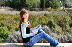 Teen girl  reading magazine. Fashion teen girl  resting in park and reading magazine Stock Images