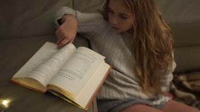 Teen girl reads a book while sitting on the floor covered with a checkered rug. Christmas, lights, home comfort.  stock video footage