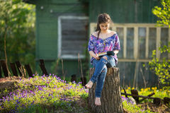 Teen girl reads book sitting on a stump in the yard in the village. Education. Royalty Free Stock Image