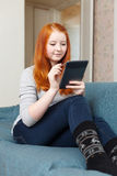 Teen girl reads e-book  or tablet computer Royalty Free Stock Photo