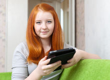 Teen girl reads e-reader or tablet computer Royalty Free Stock Image