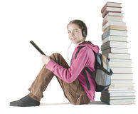 Teen girl reads ebook near the stack of books royalty free stock photo