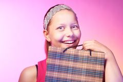 Teen girl receives a gift. Beautiful happy teen girl receives a gift on a birthday Royalty Free Stock Images