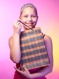 Teen girl receives a gift. Beautiful happy teen girl receives a gift on a birthday Stock Image