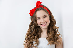 Teen girl with red bow on head. Beautiful teenage girl with long curly hair and red ribbon bow on head wearing white dress. Happy expression. Studio portrait on Royalty Free Stock Photography