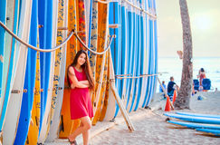Teen girl in red dress leaning by surfboards on beach Stock Images