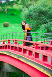 Teen girl  at a red Japanese or Chinese Bhuddist temple bridge Royalty Free Stock Images