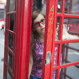 Teen girl in the red phone booth Royalty Free Stock Photos