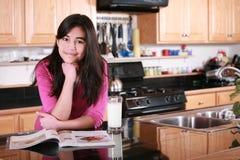 Teen girl relaxing in kitchen Stock Photos