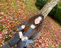 Teen Girl Relaxing Outdoors during the Autumn Season Royalty Free Stock Image