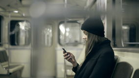 Teen girl rides the metro at night and used smartphone stock footage