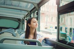 Girl rides a tourist bus and looks out the window. royalty free stock photography
