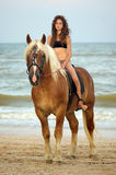 Teen girl riding a horse. Beautiful teen girl riding a horse on the beach Royalty Free Stock Image