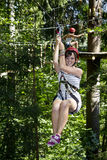 Teen Girl Riding a Zipline in the Forest Royalty Free Stock Images