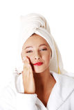 Teen girl in robe putting creme on her face. royalty free stock photos