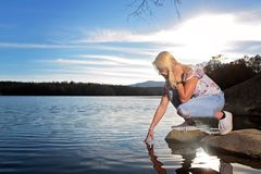 Teen girl on a rock by the lake royalty free stock photo