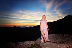 Teen girl on a rock overlook in the mountains royalty free stock photo