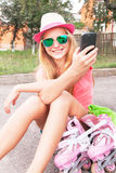 Teen (girl) with roller skating shoes using smart phone. Royalty Free Stock Photo