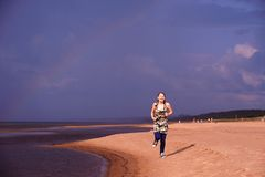 Teen girl runs along the beach Royalty Free Stock Photos