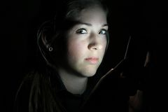 Teen Girls Face Lit by Cell Phone Stock Image