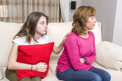 Teen girl is sad because her mother is angry while sitting on sofa at home.  royalty free stock photos