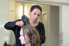 Teen Girl In Salon Drying her Hair with Blow Dryer Royalty Free Stock Photography