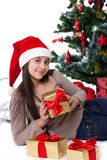 Teen girl in Santa hat with gifts under Christmas tree Royalty Free Stock Photography