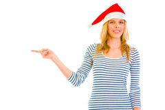 Teen girl in Santa hat pointing in corner Stock Photos