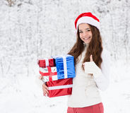 Teen girl with santa hat and red gift boxes showing thumbs up in winter forest Stock Photo