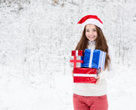 Teen girl with santa hat and red gift boxes standing in winter forest.  Stock Photography