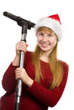 Teen girl in santa hat with vacuum cleaner Stock Images