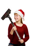 Teen girl in santa hat with vacuum cleaner Royalty Free Stock Images