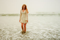 Teen girl sauntering in the waves Stock Photo
