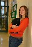 Teen Girl in School Hall. A pretty teenager leans against school corridor Stock Images