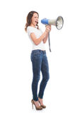 A teen girl screaming on the megaphone. A young and attractive Caucasian woman in stylish jeans screaming on the megaphone. The image is isolated on white Stock Image